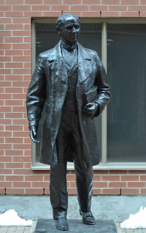 a black bronze statue of James Beaty, standing with a folded newspaper under his arm, about life sized,