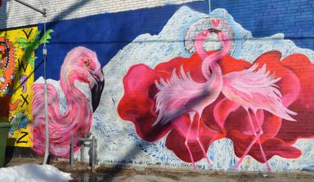 three pink flamingos. Two with entwined necks and one looking on, street art,
