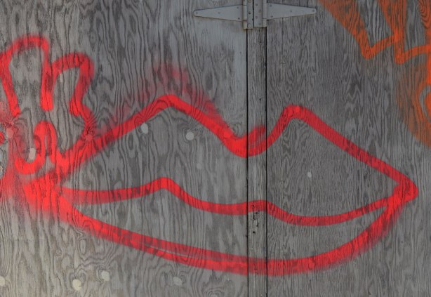 spray paint large red lips, outline drawing, on an old wood garage door in an alley