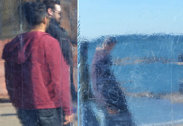 three men are reflected in a shiny surface on an art installation. Someon has scratched the word LOVE into the surface