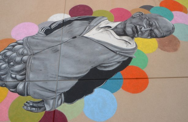 part of a larger mural by Troy Lovegates, an older man in black, white and grey floats as if he's asleep on coloured circular bubbles