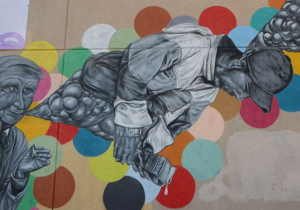 lovegates mural, people in grey tones, background of different coloured circles, man is horizontal, facing down, holding a dripping milk carton in his hand.