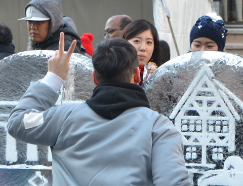 a young man stands behind an ice sculpture to pose for a picture, one hand up with peace sign of two fingers, a young woman is looking at him from the other side of the sculpture