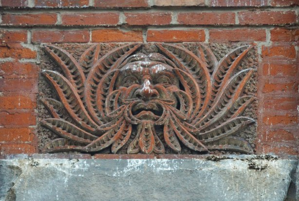 carved stone piece high on a brickwall, exterior of a building, relief sculpture of a man's face with his hair made to look like long leaves that surround his face