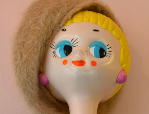 mannequin head, bright yellow short hair, blue eyes, red lips, pink ears, big smile on her face, wearing a beige tam