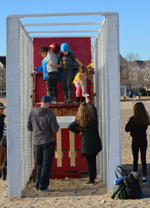 an art installation on the beach, people in winter clothes, two parallel walls about 10 feet high made of a layer of horizontally arranged empty plastic bottles with the opening facing in, people are writing on paper and then putting the messages in the bottles. view form one end, the walls enclose a lifeguard station, 4 kids are on the lifeguard platform