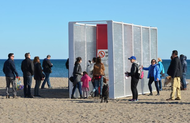 an art installation on the beach, people in winter clothes, two parallel walls about 10 feet high made of a layer of horizontally arranged empty plastic bottles with the opening facing in, people are writing on paper and then putting the messages in the bottles.