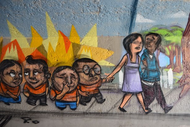 mural by elicser in the tunnel that is a railway underpass - a mother and father lead a group of noisy kids on a walk