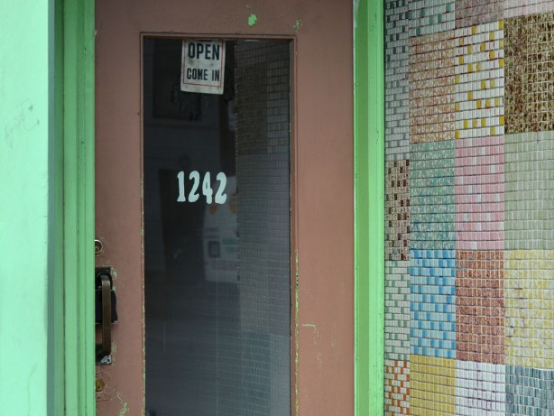 a door with 1242 on it, brownish colour, green door frame, the wall on one side is covered with small mosaic tiles in squares