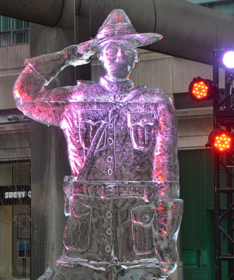 a ice sculpture of a mountie standing at attention and saluting, light by pink and red lights,