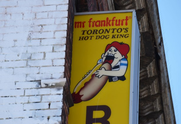a large yellow sign for Mr. Frankfurt restaurant showing a red headed girl trying to eat a hot dog that is larger than she is. yellow sign attached to building.
