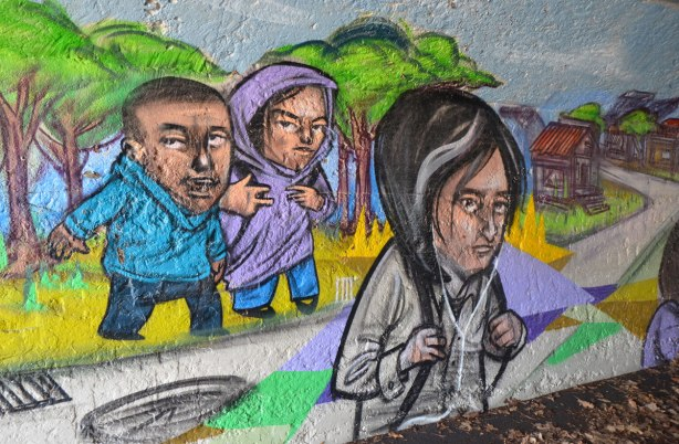 mural by elicser in the tunnel that is a railway underpass - young people walking, one with earbuds on and one making hand signs