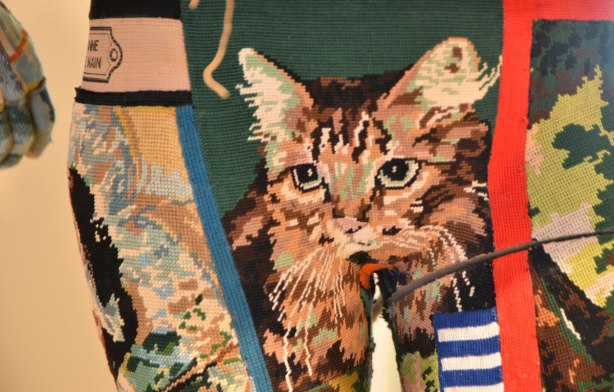 close up of part of a mannequin dressed in tight fighting fabric made of a patchwork of tapestry pieces. The piece shown in this image is of a brown cat
