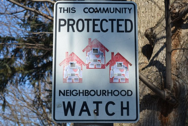 a neighbourhood watch sign posted on a hydro pole, a lovebot sticker is on each of the three houses on the sign