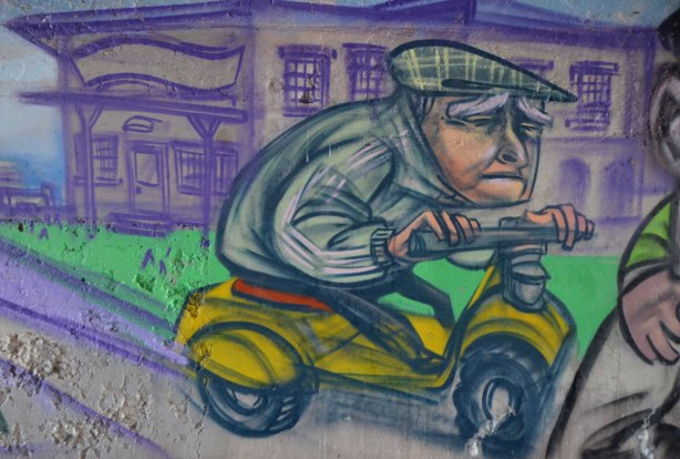 mural by elicser in the tunnel that is a railway underpass - an older man on a motorized scooter, he looks sad, frowning.