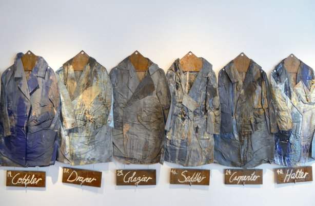 a row of dirty well used workcoats that used to be blue are hanging on the wall of an art gallery. under each one is a label with a job name, draper,