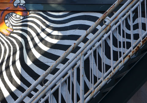 a white staircase is diagonal in the picture, with white metal bars and railng, immediately behind it is a street art picture of an orange face blowing down towards the stairs. White wavy lines radiate from the open mouth