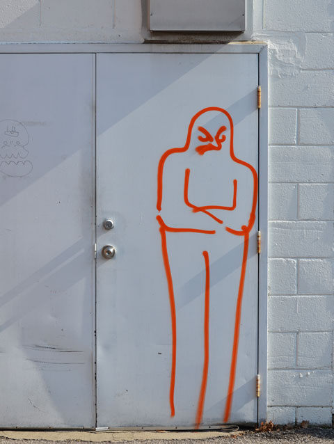 a white metal door on a white concrete wall. A bright ornage line drawing of a man standing in front of the door with his arms crossed.