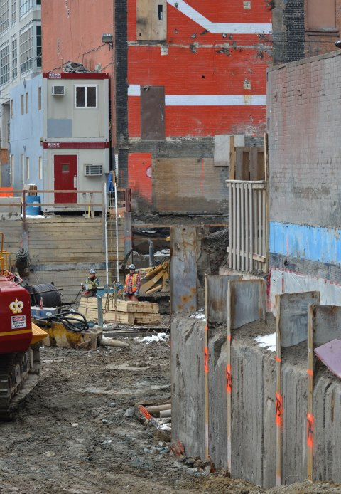 a large construction site at Victoria and Lombard, one wall of a neighbouring building has been exposed that is orange and white