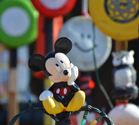 a mickey mouse plastic figure is sitting on a wire fence, his chin is his hand and he's looking upwards, other toys out of focus behind him - circles with happy faces and a couple of frisbees