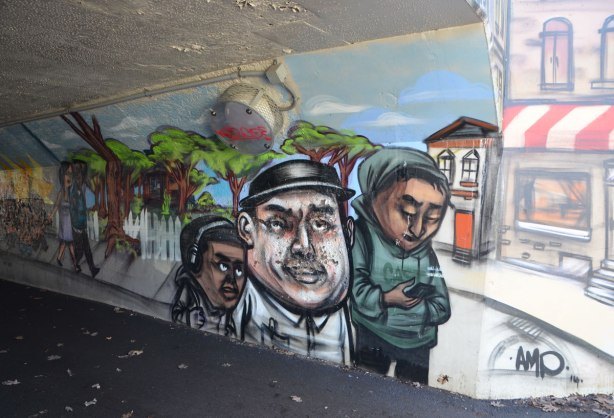 mural by elicser in the tunnel that is a railway underpass - people walking outside