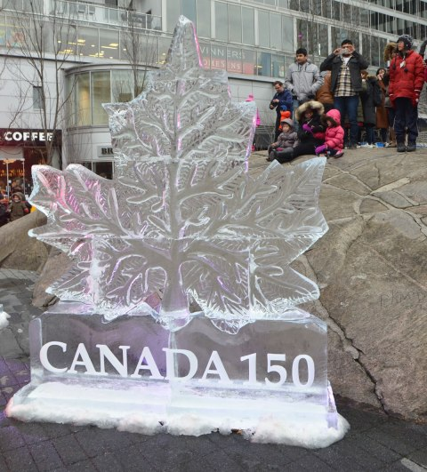 a group of people sit and stand on a large rock behind an ice sculpture of a maple leaf with the words Canada 150 under it, all carved in ice.