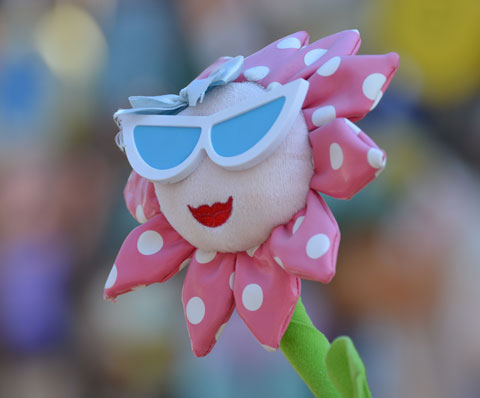 a toy flower with a green stem, petals made of pink fabric with white polka dots, red lips and large white and blue sunglasses.