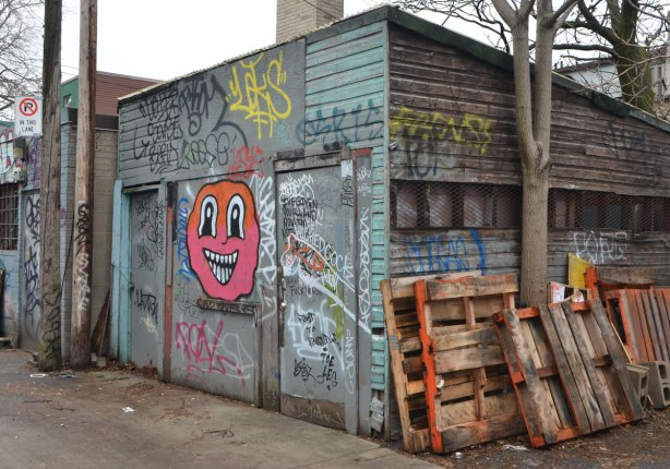 garage in an alley with a big pink and orange face with black and white eyes and big smiling mouth with lots of white teeth