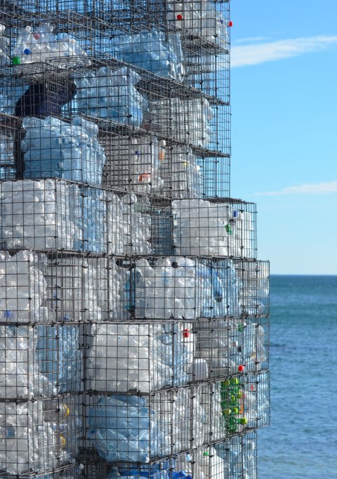 a tower of plastic bottle filled wire cages stands in front of Lake Ontario