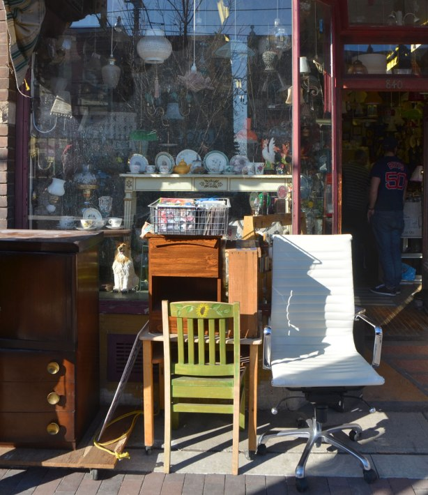 chairs and a set of drawers outside a store full of antiques and stuff, the door is open and you can see into the store where there are two men shopping.