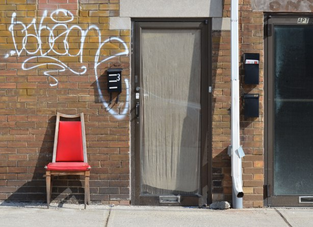 a bright red chair sits on the sidewalk beside the entrance to a building. The door has a large window which is covered by a curtain on the inside