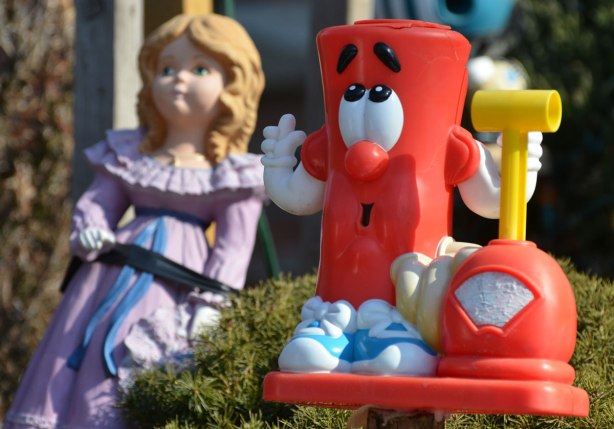 a red plastic toy in the foreground, a doll in a purple dress in the background
