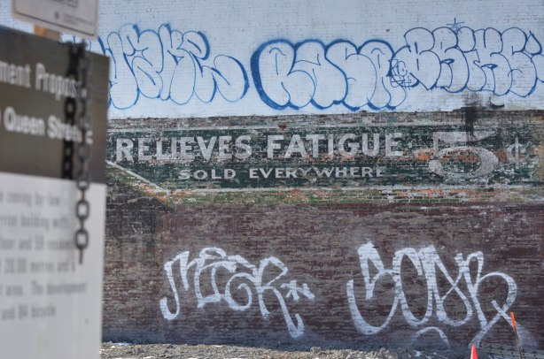 an old wall has been exposed after a building has been demolished. The sign is part of an old coca cola advertisement and says relieves fatigue 5 cents.