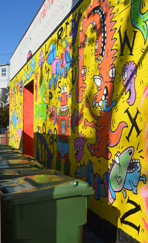 a mural by runt on a bright yellow background with letters of the alphabet in black and many imaginary creatures in bright colours.