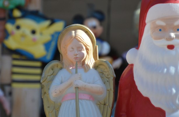 a plastic Santa Claus, a plastic angel and a pokemon