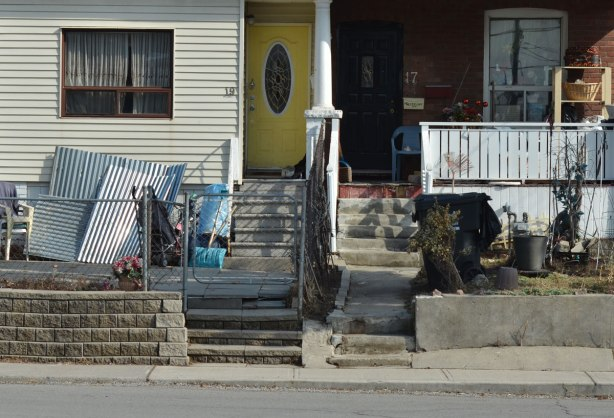 a semi divided house, on the left, a bright yellow door. On the right, an open porch with lots of clutter.