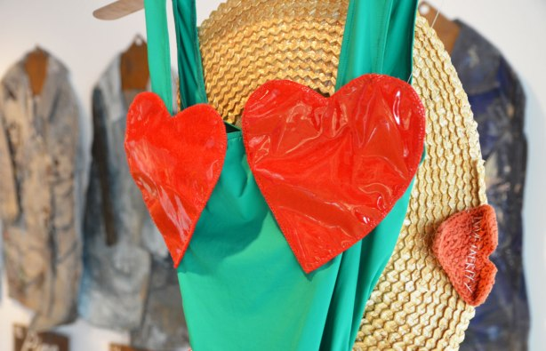 a straw hat hangs with a dress made of green fabric, sleeveless, with two big shiny red hearts that would cover the breasts of the woman who wore it.