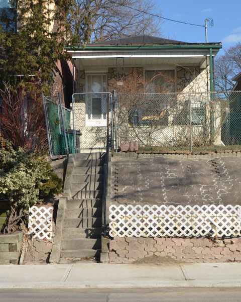 a small narrow one storey house. Many steps to get up the hill to the front door. The incline has been covered with patio stones.