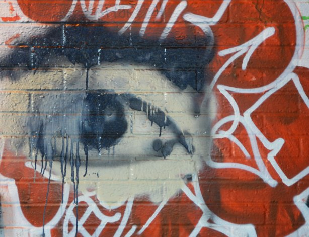a black and white eye graffiti painting, smudged and with dripping paint, red background