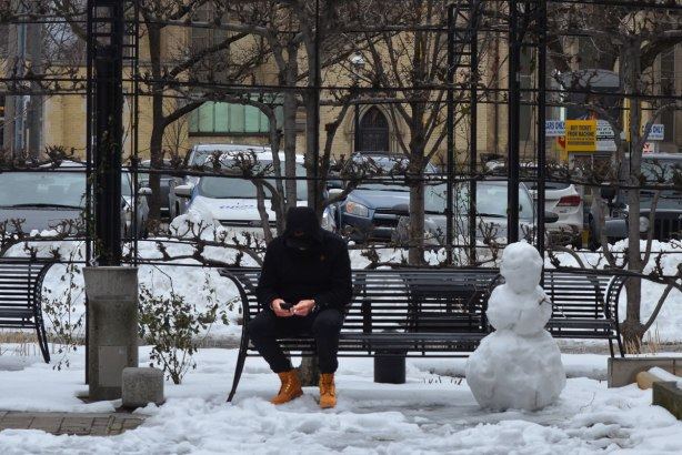 a man sits on a bench in a small park, wintertime, a snowman is at the other end of the bench