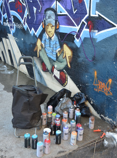 part of a mural of a boy with headphones on, seat crossed legged on the ground and pointing downwards. He seems to be pointing at a collection of spray paint cans sitting on the ground below the mural.