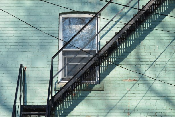 shadows on a sunny day, a metal fire escape is diagonal across the back of a light teal coloured house, it passes the bottom corner of a window