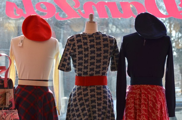 looking out a store window, 3 headless mannequins are in the window, dresses in women's clothing, one has a red tam on her shoulders, one has a dress with a repeating pattern of typewriters, one has a red skirt with with white hearts all over it.