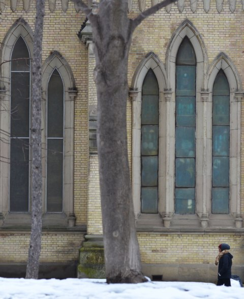 vertical stained glass windows of St. James cathedral, from the outside in winter, a woman is walking past.