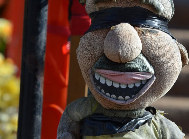 a stuffed plushie creature is attached to a pole with black electrical tape around his face such that it covers his eyes