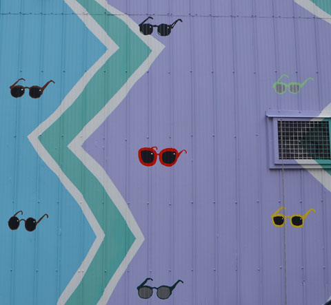 little sunglasses painted on a lilac coloured wall