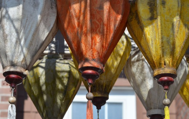 hanging lantern shapes made of fabric, with tassles at the bottoms, hanging over a gate, yellow, green, orange and white