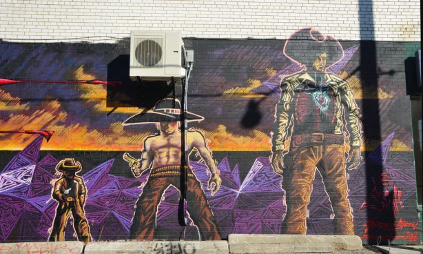 a mural of three cowboys, one tall, one in the middle and one short, purple and orange scenery behind them.