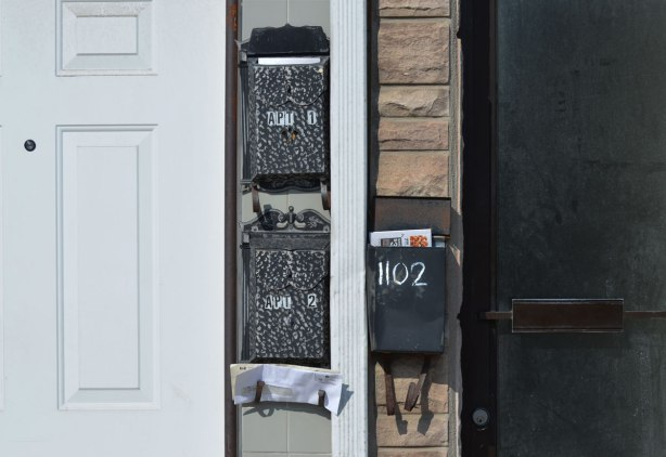 three black mailboxes with mail in them, between a white door and a black door.