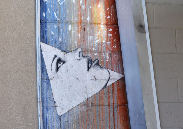 street art picture of a triangular shaped face looking upwards, open eyes and partially open mouth, behind the face is streaks of blue, yellow and red.